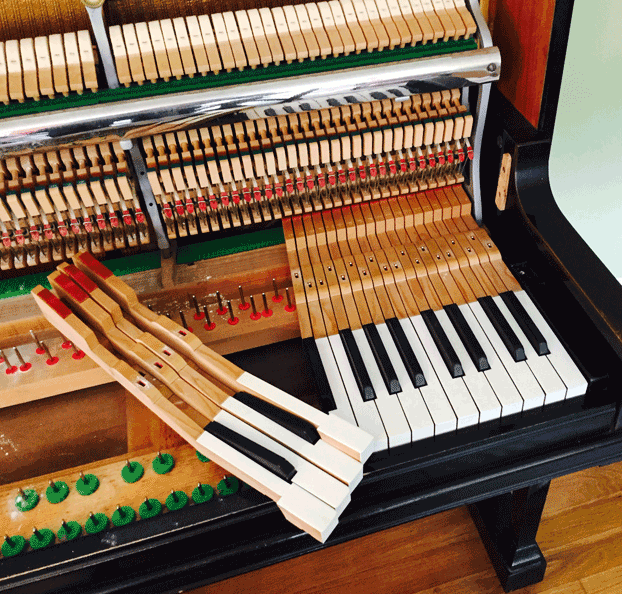 keys out of the upright piano ready for servicing